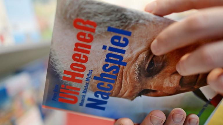 Ein Besucher der Leipziger Buchmesse liest am 13.03.2014 in Leipzig (Sachsen) am Stand des Verlages Ellert&Richter in einem Portrait über den Fußballmanager Uli Hoeneß.