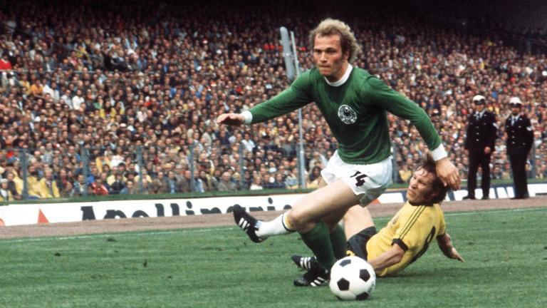 Der deutsche Mittelfeldspieler Uli Hoeneß (vorn) kommt vor dem australischen Mittelfeldakteur James Mackay an den Ball. Die deutsche Fußballnationalmannschaft gewinnt am 18.06.1974 vor 53.300 Zuschauern im Hamburger Volksparkstadion das WM-Gruppenspiel gegen Australien mit 3:0.