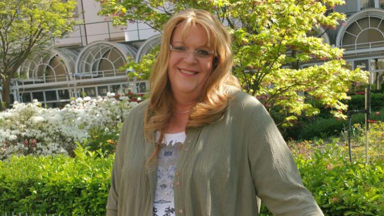 Foto von Claudia mit einem strahlenden Lächeln
