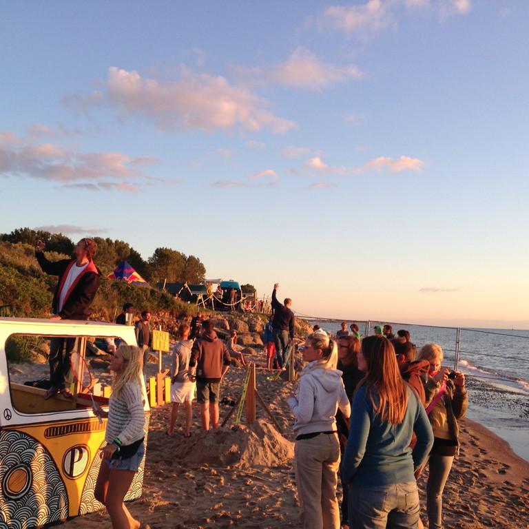 Menschen stehen an der Ostsee bei Sonnenuntergang