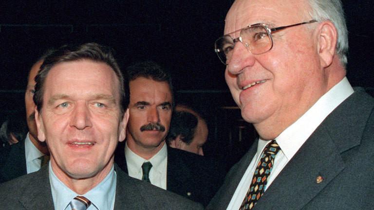 Bundeskanzler Helmut Kohl (r) und Niedersachsens Ministerpräsident Gerhard Schröder begegnen sich am 18.3.1998 bei der Eröffnungsfeier der CeBIT-Messe in Hannover. In seiner Eröffnungsrede zur weltgrößten Computermesse kritisierte Kohl die Steuervorschläge des SPD-Wahlprogramms als völlig unzureichend. Ohne die SPD zu nennen, bezeichzete er eine Senkung des Spitzensteuersatzes von 53 auf 49 Prozent als bedeutungslos. Notwendig sei eine wesentlich stärkere Senkung des Spitzensteuersatzes nach dem Vorbild europäischer Nachbarländer.