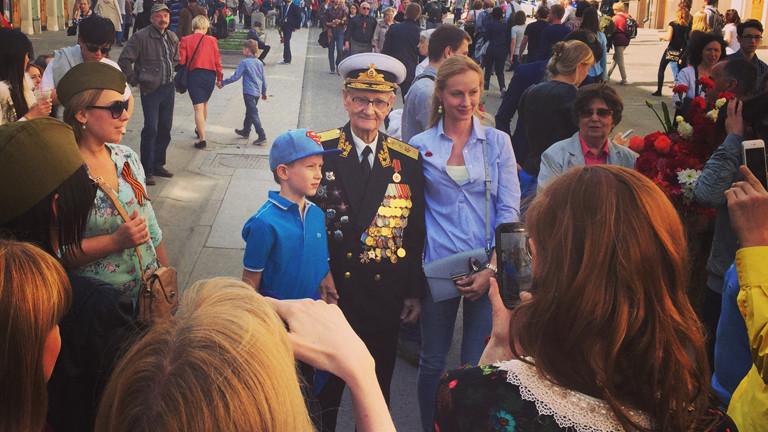 Ein alter Mann in Uniform, über und über behängt mit Orden, neben ihm ein kleiner Junge.