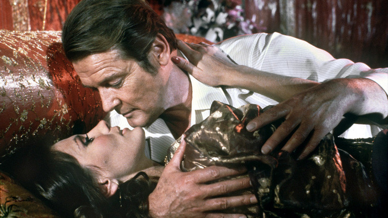 """Als gewohnt erfolgreicher Verführer agiert Roger Moore als Agent 007 in einer Szene mit Maud Adams in dem James Bond-Film """"Octopussy"""" (1983)."""