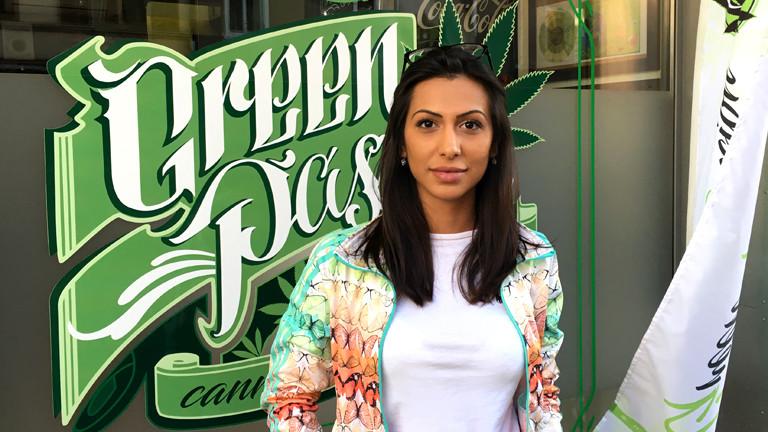 Eine Frau vor einem Schaufenster mit einem Hanfblatt