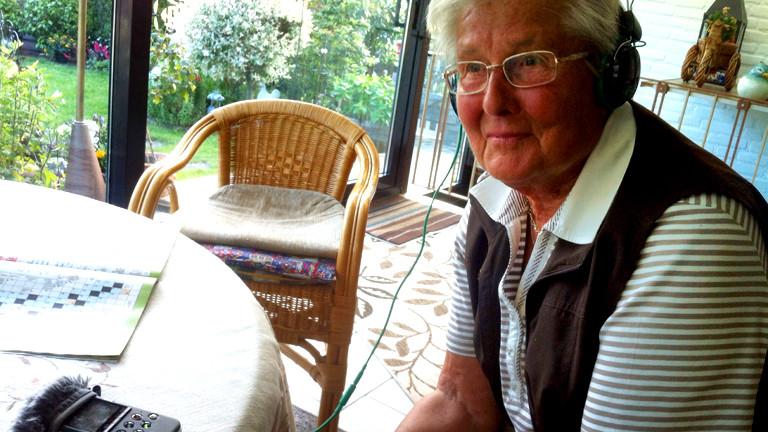 Noras Oma sitzt mit Kopfhörern vor dem Aufnahmegerät
