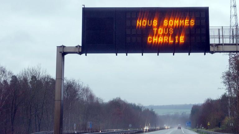 """Auf der französischen Autobahn E25 Autoroute de l'Est leuchtet am 08.01.2015 in Höhe Hombourg-Haut der Schriftzug """"Nous sommes tous Charlie"""