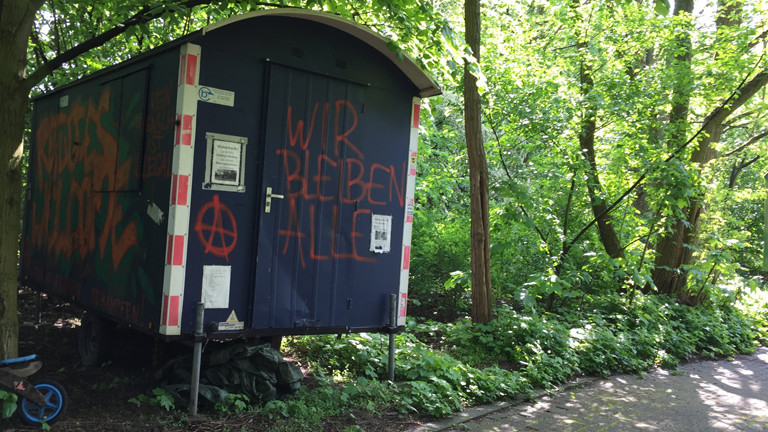 """Bauwagen mit der Aufschrift """"Wir bleiben alle"""""""