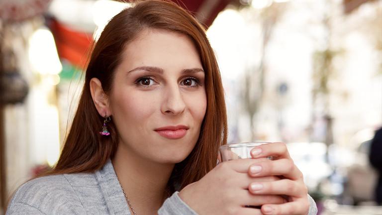 Hannah Winkler lächelt in einem Kaffee in die Kamera