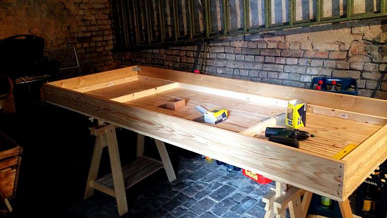 Auf zwei Holzböcken ist ein Kasten befestigt, etwa so groß wie eine schmale Matratze, darin liegt Werkzeug.