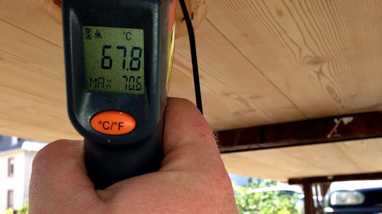 Unterhalb des Solarluftkollektors misst Holger Beetz mit einem elektronischen Thermostat die Temperatur im Kollektor.