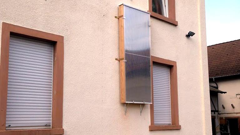 An der Hauswand hängt der fertige Solarluftkollektor