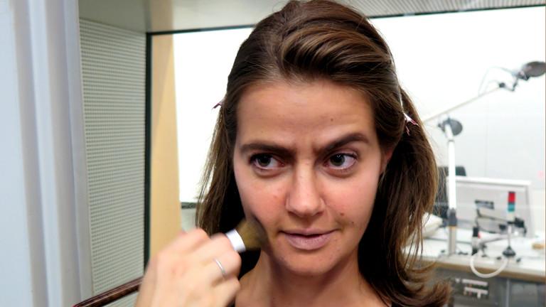 Florence schminkt mit einem Pinsel Julias rechte Wange dunkel nach