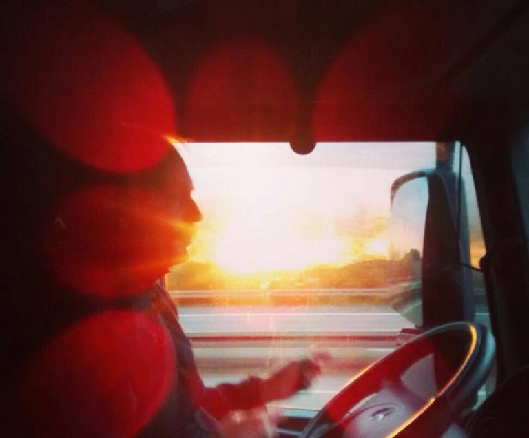 Roberto in seinem LKW, durch das Fahrerfenster scheint die tiefstehende Sonne