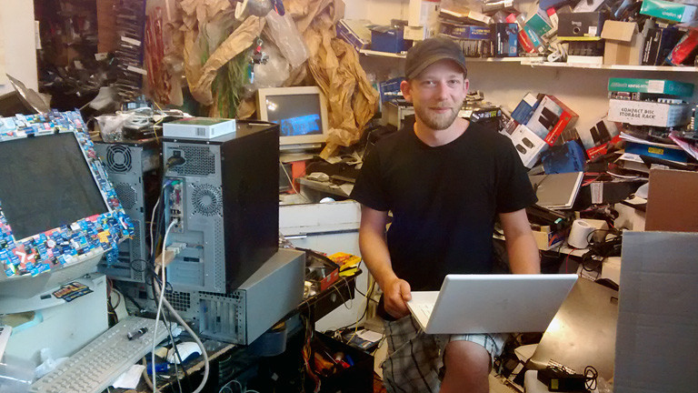 Mann zwischen Computereinzelteilen und Laptops