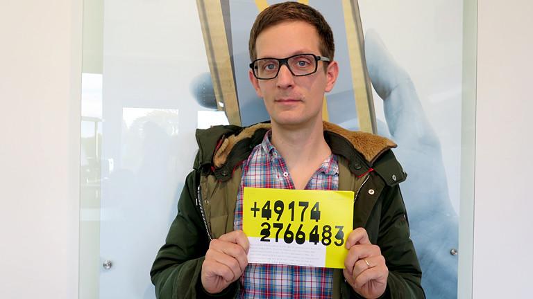 Ein Mann hält einen Zettel mit einer Handynummer