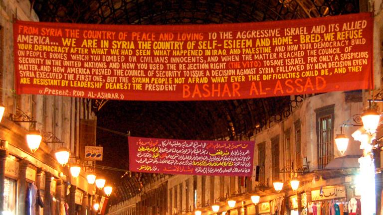 Auf einem Banner steht ein Text, Propaganda der syrischen Regierung. Er beginnt mit: Aus Syrien, dem Land des Frieden und der Liebe.