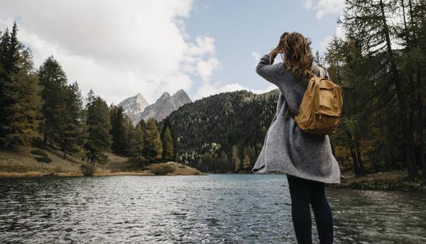 Frau steht in den Bergen an einem Waldsee.