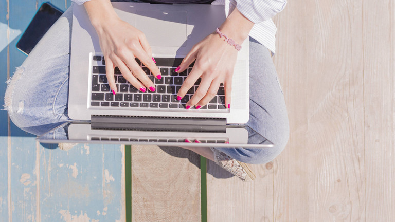 Frauenhände tippen auf Laptop