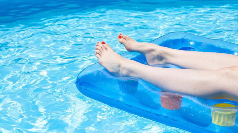 Die Beine einer Frau, die auf einer Luftmatratze im Pool liegt.