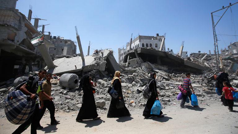 Menschen im Gazastreifen tragen ihr Hab und Gut an einem zerstörten Haus vorbei.