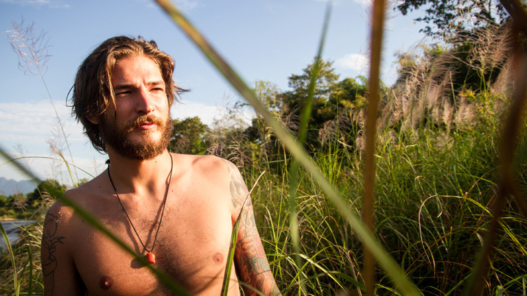Ein Mann mit Bart, Tattoos und Brusthaaren.