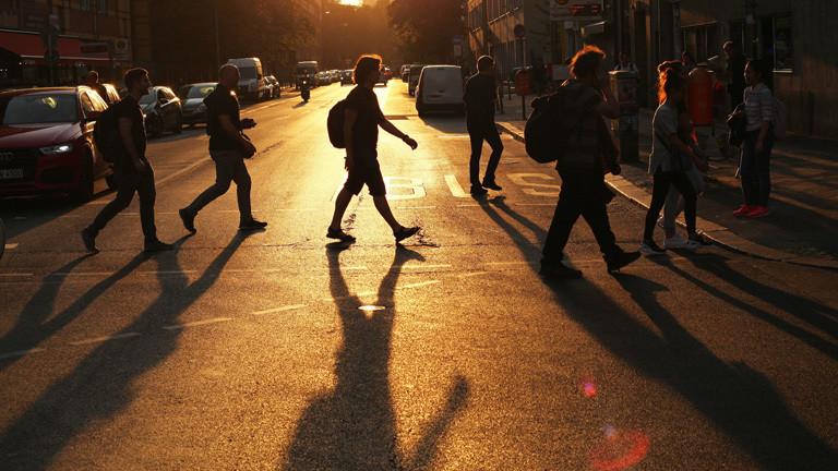Fußgänger, die eine Straße überqueren - im Abendlicht.
