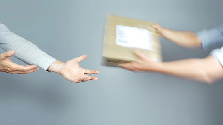 Zwei Hände reichen zwei anderen Händen ein Päckchen.