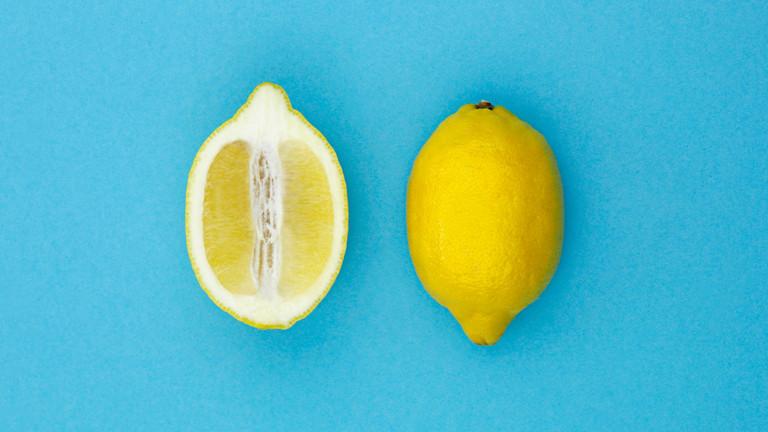 Eine aufgeschnittene und eine ganze Zitrone