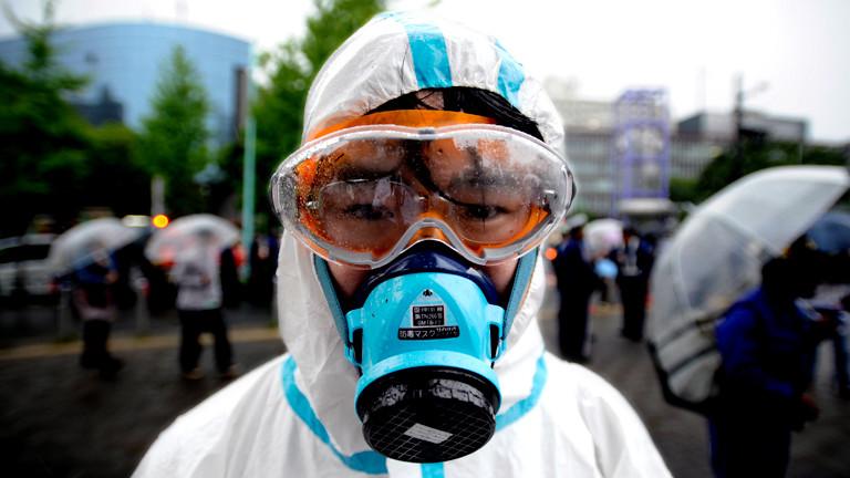 Ein Mann mit Atemmaske, Schutzanzug und Schutzbrille schaut in die Kamera, Bild: dpa