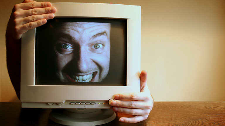 Das Gesicht eines lachenden Mannes auf einem Computerbildschirm.