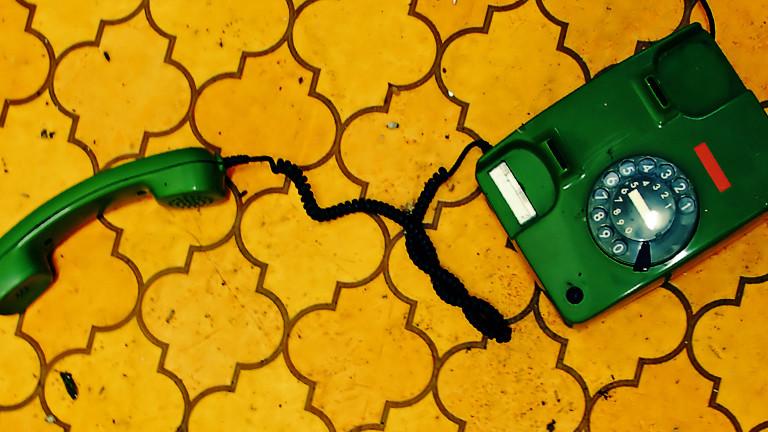 Ein altes, grünes Telefon mit Wählscheibe liegt auf einem schmuddeligen Fußboden.