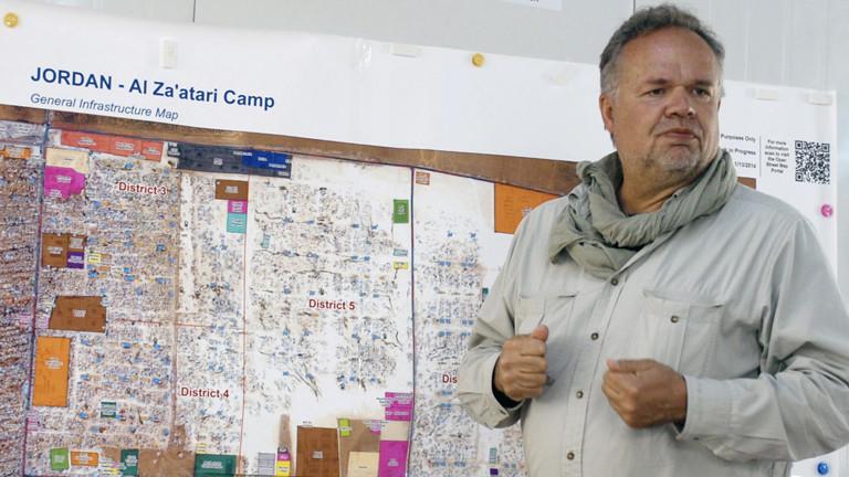 Kilian Kleinschmidt vor einer Wand mit Plänen vom Flüchtlingslager.