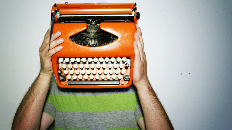 Mann, der sich eine orange Schreibmaschine vor das Gesicht hält.