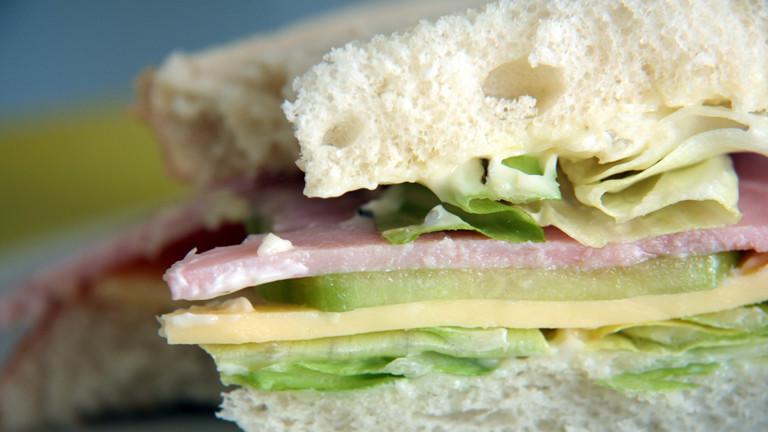 Sandwich mit Käse, Schinken, Gurke und Salat.