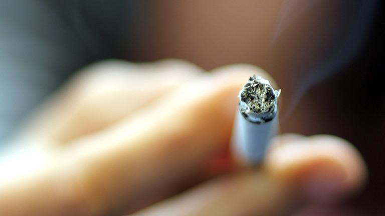 Jemand hält eine qualmende Zigarette in der Hand.