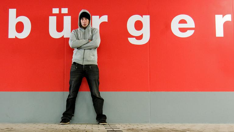"""Ein Mann hat sich an eine rote Wand gelehnt, auf der """"bürger"""" steht."""
