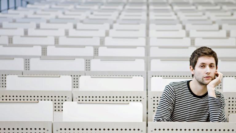 Ein Student sitzt recht gelangweilt in einem sonst leeren Hörsaal.