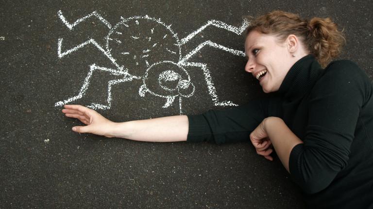 Eine Frau hat Angst vor einer großen, gemalten Spinne.
