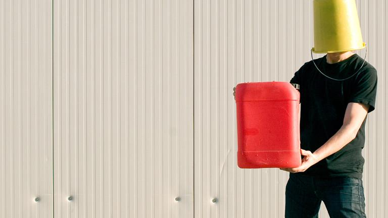 Ein Mann mit Eimer auf dem Kopf präsentiert einen Plastik-Kanister.