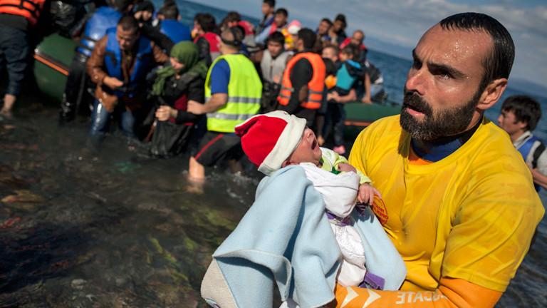 Am 29.10.2015 kommen Flüchtlinge auf Lesbos an, ein frewilliger Helfer hält ein Baby in den Armen.