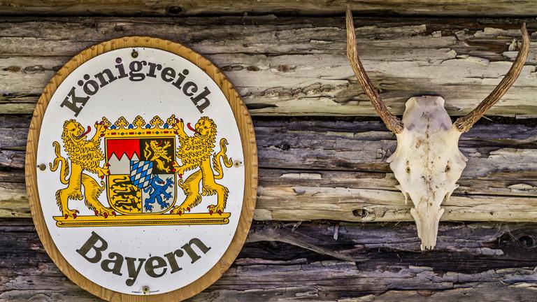 Ein Schild mit der Aufschrift Königreich Bayern hängt neben einem Hirschgeweih