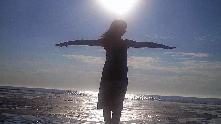 Eine Frau steht mit gestreckten Armen unter der Sonne