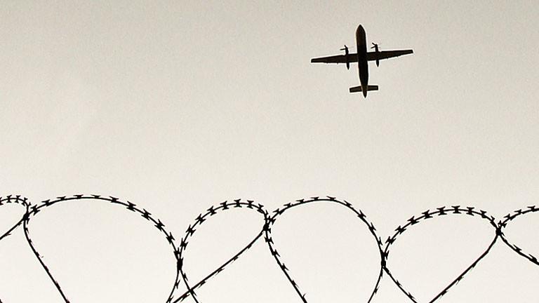 Flugzeug fliegt über Stacheldraht