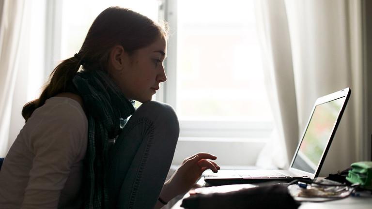 Eine Frau sitzt vor einem Laptop.