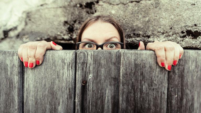 Eine Frau guckt über einen Zaun.