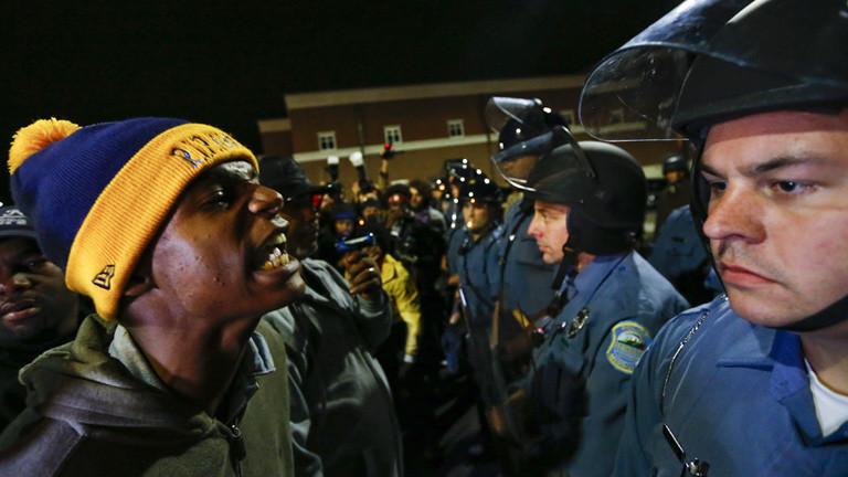 Bei einem Protest in der US-Stadt Ferguson (10.10.2014) stehen sich Demonstranten und Polizisten gegenüber. Einer der Demonstranten spricht auf einen der Polizisten ein; Foto: dpa