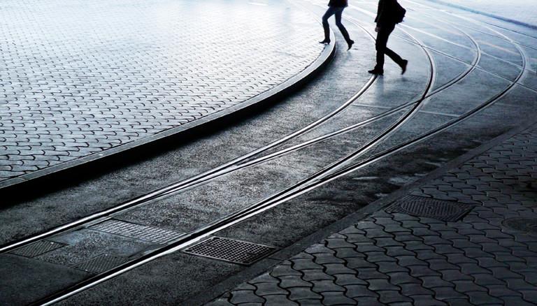 Zwei Fußgänger überqueren Straßenbahnschienen.