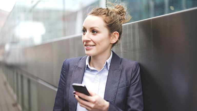 Frau lehnt an einer Mauer mit Smartphone in der Hand