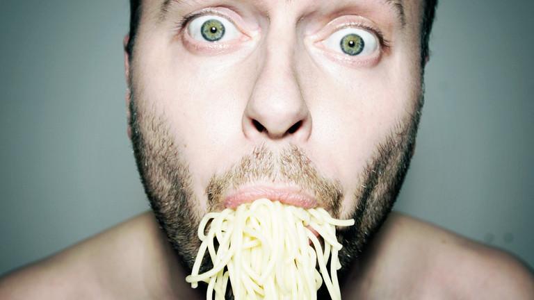 Mann mit einem Mund voll Spaghetti.