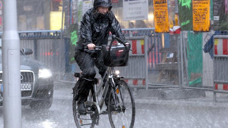 Frau fährt bei Regen in Berlin Fahrrad.